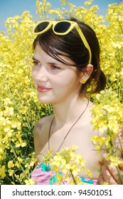 A young caucasian girl in a field of spring canola flowers.