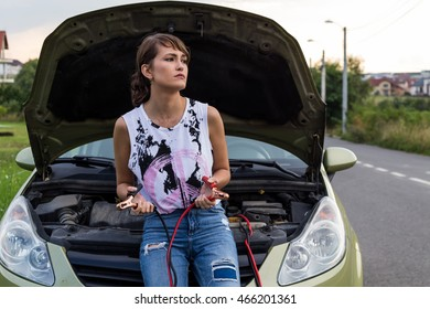 Young caucasian girl in front of her car. Hood popped up. Jump cable. Broken car.