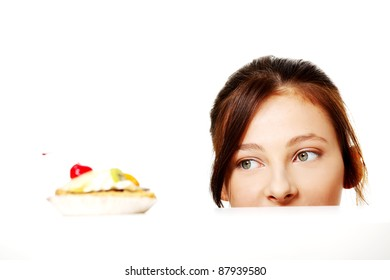 Young caucasian girl hiding behind the desk and looking at the cake over white.
