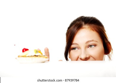 Young caucasian girl hiding behind the desk and reaching for the cake over white.