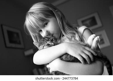 young caucasian girl holding a tabby kitten