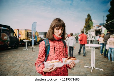 Young Caucasian Girl Holds Two Sandwiches Or A Hamburger In Her Hands And Looks At Them By Smacking At A Festival Of Street Food.