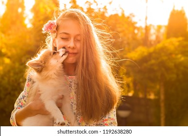 Young caucasian girl with a long blond hair holding a puppy outdoor in the autumn garden. Dog licking child's face - happy childhood concept. Gold sunset light.