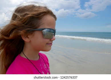Young Caucasian girl with long hair and sunglasses looking at the beach and ocean in Florida