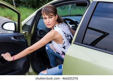 Young caucasian girl looking back. Car door open.