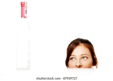Young caucasian girl looking at the bottle with alcohol.
