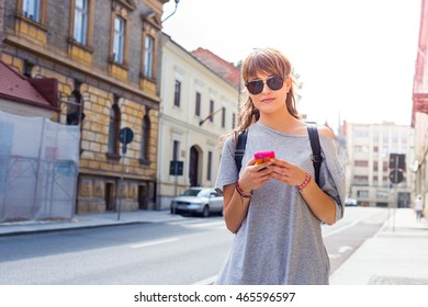 Young caucasian girl with a mobile smart phone on the street