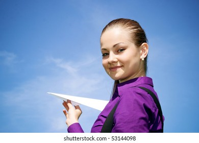 Young caucasian girl with paper plane in the hand