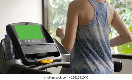 Young caucasian girl running on the treadmill in the sport gym