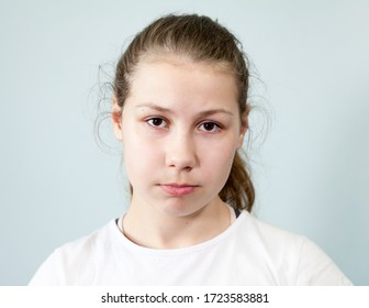 Young Caucasian girl with a sad expression on her face. Portrait on grey background, emotions series.