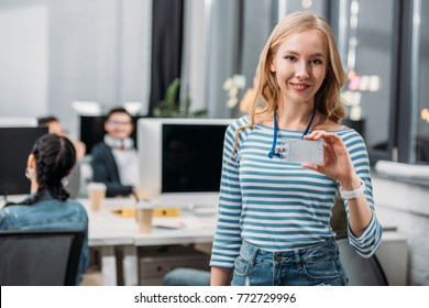 young caucasian girl showing name tag at modern office