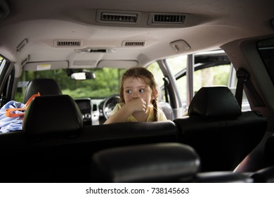 Young caucasian girl sitting thoughtful inside the car