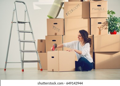 Young Caucasian girl using duct tape for packing carton boxes