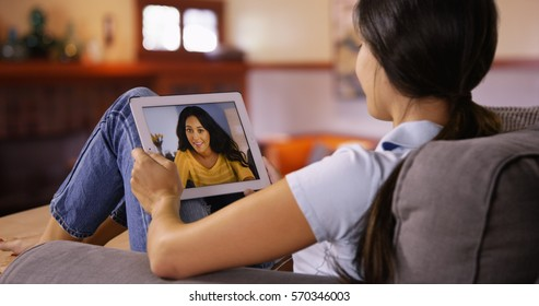 Young Caucasian girl video chats with her friend on her tablet