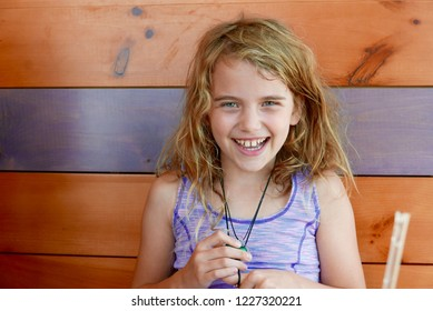 Young Caucasian girl with wavy blonde hair smiling and laughing in front of a wood-paneled wall, looking at the camera