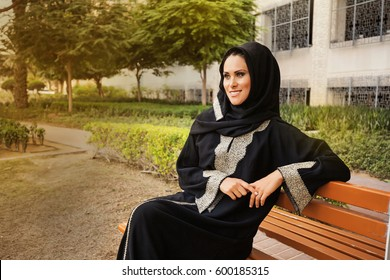young Caucasian girl wearing hijab and jilbab sitting on a bench smiling in a park