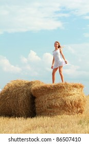 young caucasian girl in white transparent dress dancing on bale of straw