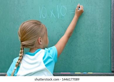 Young Caucasian girl writing math problem on green chalkboard