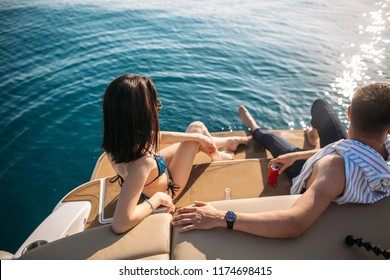 Young caucasian good-looking man and his beautiful girlfriend in bikini sunbathing on yacht. Happy couple on vacation with beautiful sea views of calm blue water