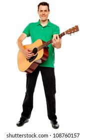 Young caucasian guitarist playing tracks isolated over white background