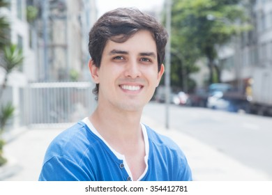 Young caucasian guy with blue shirt in city