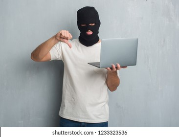 Young caucasian hacker man over grey grunge wall doing cyber attack using laptop with angry face, negative sign showing dislike with thumbs down, rejection concept