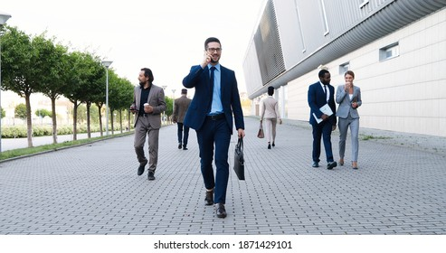 Young Caucasian handsome happy businessman walking in morning in city outdoors and talking on mobile phone. Attractive cheerful man speaking on cellphone and strolling among people to work.