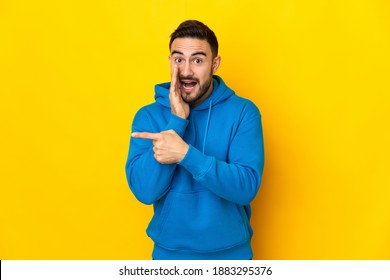 Young caucasian handsome man isolated on yellow background pointing to the side to present a product and whispering something