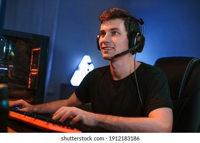 Young Caucasian handsome professional cybersport player training or playing online video game on his PC, participate in team play, preparing for tournaments. Vlogger streaming his game. Cyber sport