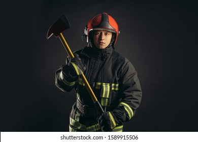 young caucasian handsome and strong fireman in uniform wearing helmet on head hold hammer in hands, going to save people from fire