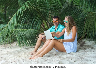 Young caucasian happy couple on the beach enjoying the laptop