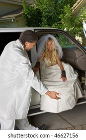 Young Caucasian happy newlywed woman in white gorgeous wedding gown sitting in car