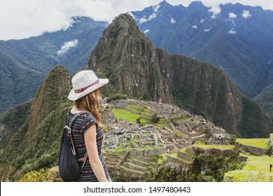 Young caucasian happy woman standing in Machu Picchu mountain. Free solo female tourist in casual hat back view with copy space. Joyful adventure vocations in Peru