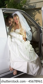 Young Caucasian happy woman in white gorgeous wedding gown sitting in car