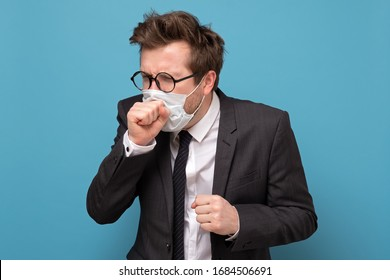 Young caucasian having a terrible dry cough wearing medical mask. Studio shot on blue wall.