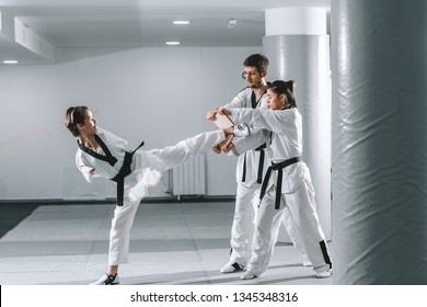 Young Caucasian highly motivated armless young woman kicking wooden board while two her friends from club holding it. Taekwondo class.