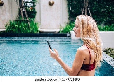 Young caucasian hipster girl blogging in social networks using smartphone standing in waterpool during vacations, attractive millennial woman satisfied with waterproof mobile phone read social media