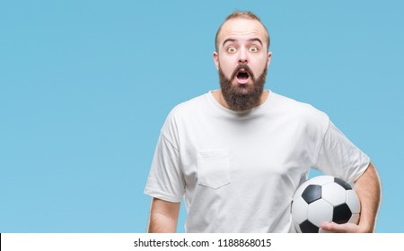 Young caucasian hipster man holding soccer football ball over isolated background scared in shock with a surprise face, afraid and excited with fear expression