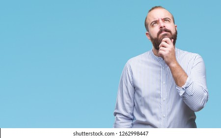 Young caucasian hipster man over isolated background with hand on chin thinking about question, pensive expression. Smiling with thoughtful face. Doubt concept.