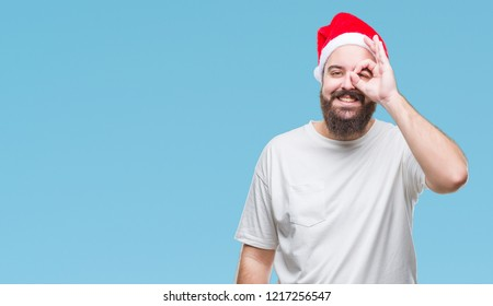 28137ddba48 Young caucasian hipster man wearing christmas hat over isolated background  doing ok gesture with hand smiling