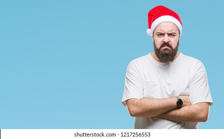 Young caucasian hipster man wearing christmas hat over isolated background skeptic and nervous, disapproving expression on face with crossed arms. Negative person.