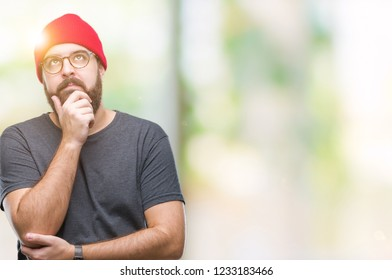 dacbc56e0b6 Young caucasian hipster man wearing glasses over isolated background with  hand on chin thinking about question