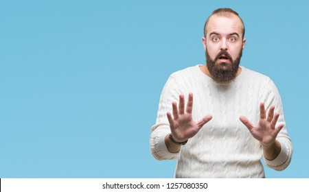 Young caucasian hipster man wearing winter sweater over isolated background afraid and terrified with fear expression stop gesture with hands, shouting in shock. Panic concept.