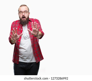 Young caucasian hipster man wearing glasses over isolated background afraid and terrified with fear expression stop gesture with hands, shouting in shock. Panic concept.