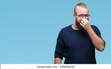 Young caucasian hipster man wearing sunglasses over isolated background smelling something stinky and disgusting, intolerable smell, holding breath with fingers on nose. Bad smells concept.