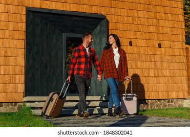Young caucasian lovely couple with luggage leaving house for joint vacation. Happy family concept.