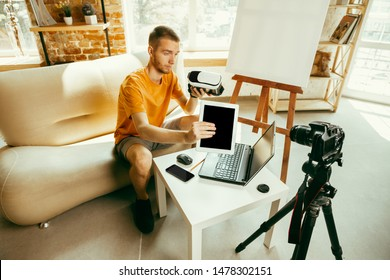 Young caucasian male blogger with professional equipment recording video review of VR glasses at home. Blogging, videoblog, vlogging. Man making vlog or live stream about photo or technical novelty.