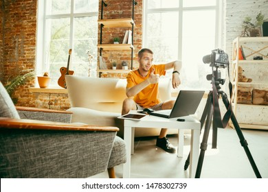 Young caucasian male blogger with professional camera recording video review of fitness tracker at home. Blogging, videoblog, vlogging. Man making vlog or live stream about photo or technical novelty.