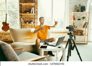 Young caucasian male blogger with professional camera recording video review of gadgets at home. Blogging, videoblog, vlogging. Man making vlog or live stream about photo or technical novelty.