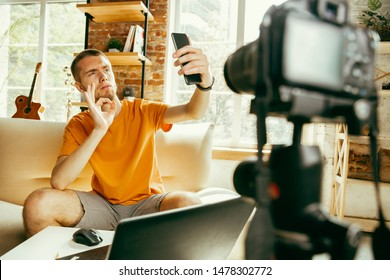 Young caucasian male blogger with professional camera recording video review of smartphone at home. Blogging, videoblog, vlogging. Man making vlog or live stream about photo or technical novelty.